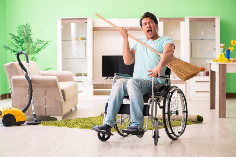 L'uomo disabile sul fare piazza pulita della sedia a rotelle fotografia stock