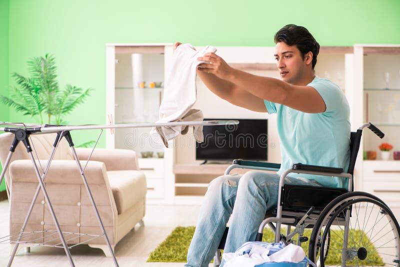 L'uomo disabile sulla sedia a rotelle che fa lavanderia fotografia stock