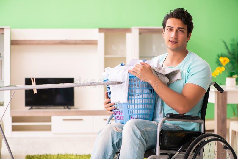 L'uomo disabile sulla sedia a rotelle che fa lavanderia immagine stock libera da diritti