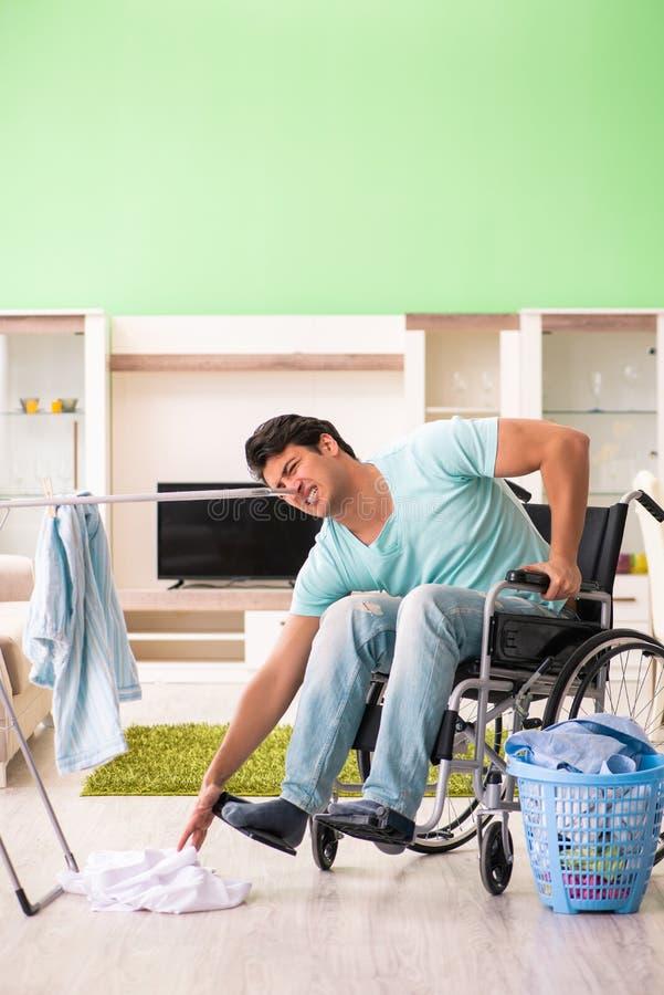 L'uomo disabile sulla sedia a rotelle che fa lavanderia fotografia stock libera da diritti