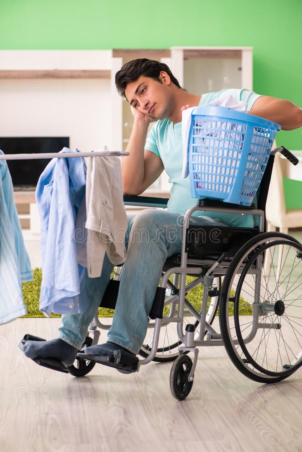 L'uomo disabile sulla sedia a rotelle che fa lavanderia immagini stock libere da diritti