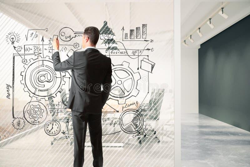 L'uomo disegna il business plan su un divisore in vetro nella sala riunioni fotografia stock libera da diritti