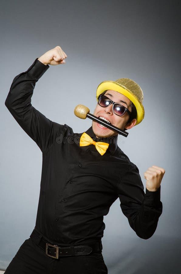L'uomo divertente con il mic nel concetto di karaoke immagini stock libere da diritti
