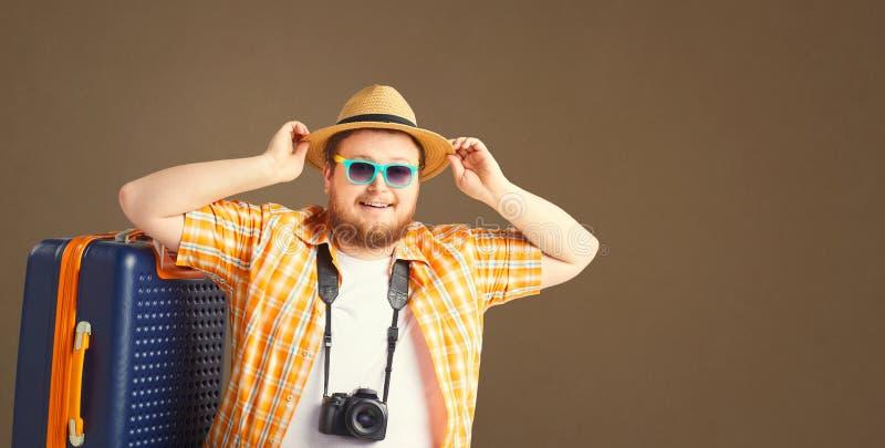 L'uomo divertente grasso sorridere della valigia va su un fondo grigio fotografia stock libera da diritti