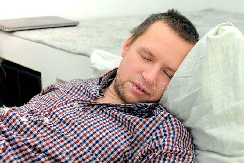 L'uomo dorme sul pavimento in salone Postumi di una sbornia dopo un partito immagini stock libere da diritti