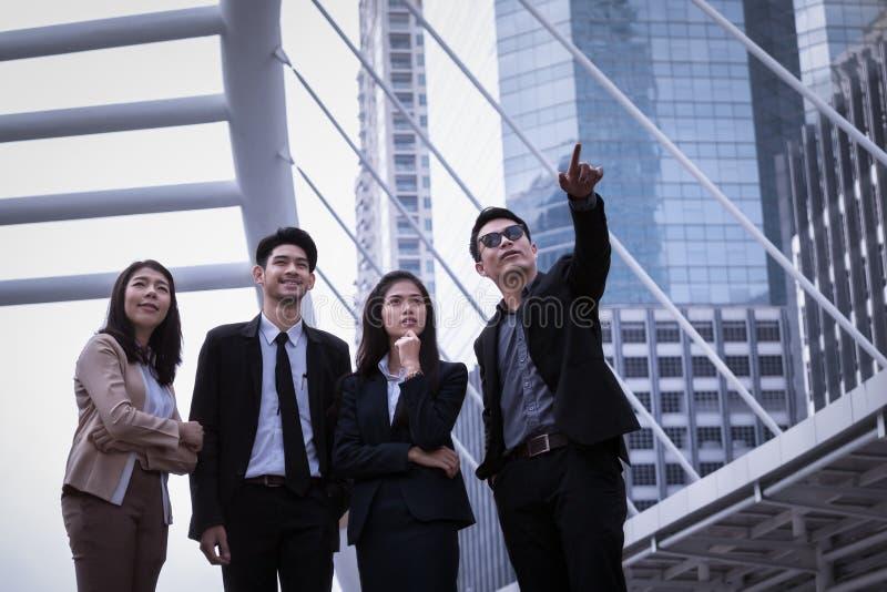 L'uomo e la donna asiatici di affari raggruppano la condizione sulla terra ed alla probabilità di intercettazione immagine stock