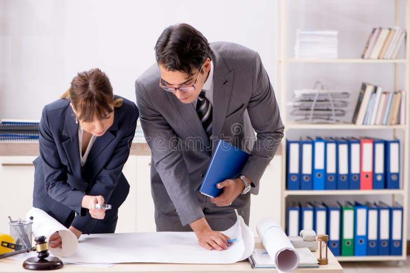 L'uomo e la donna che discutono progetto di costruzione fotografie stock