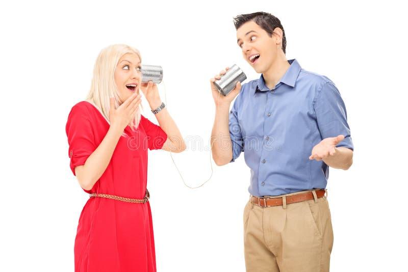L'uomo e la donna che parlano attraverso un barattolo di latta telefonano fotografie stock