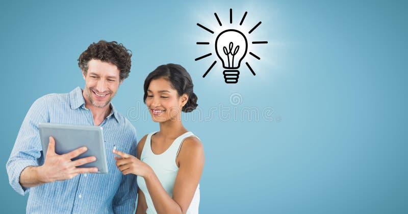 L'uomo e la donna con la compressa e la lampadina scarabocchiano con il chiarore contro fondo blu fotografia stock
