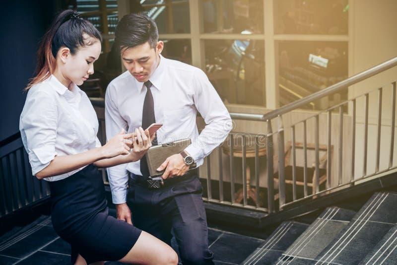 L'uomo e la donna di affari che per mezzo dello smartphone che sta parlante e rivaleggiano fotografia stock libera da diritti