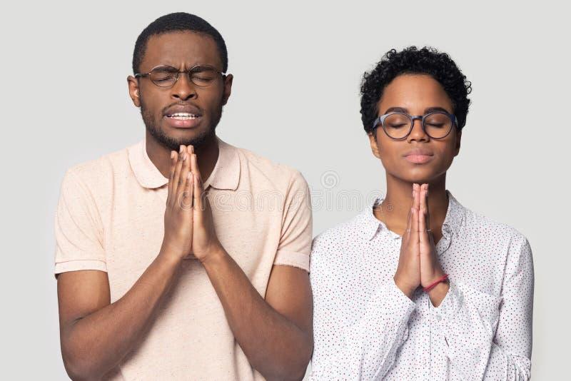 L'uomo e la donna etnici promettenti si tengono per mano nella preghiera immagine stock libera da diritti