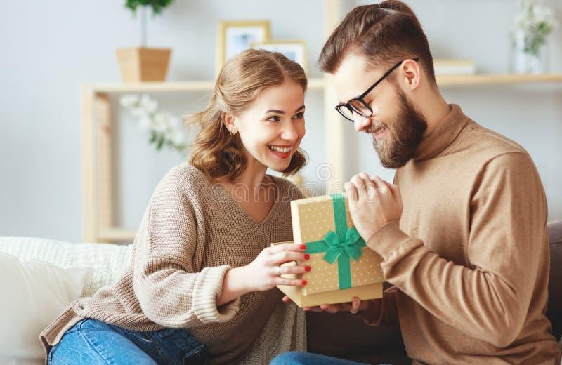 L'uomo e la donna felici della coppia sposata danno un regalo per la festa immagini stock libere da diritti