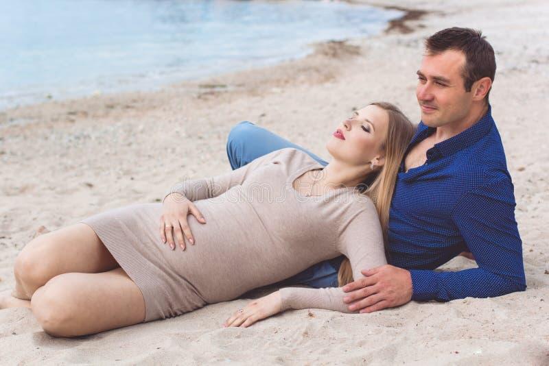 L'uomo e la donna incinta stanno riposando sulla spiaggia immagini stock