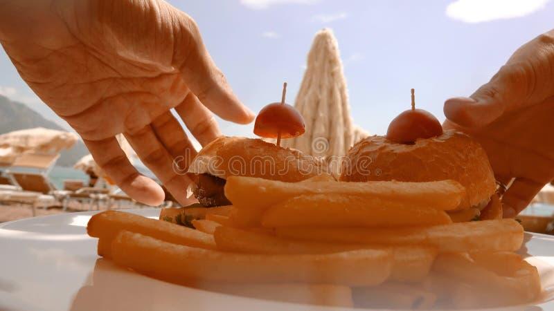 L'uomo e la donna mangiano gli hamburger sulla spiaggia immagine stock