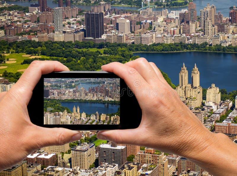 L'uomo e la donna passano la cattura di New York orizzonte aereo con smartp fotografie stock libere da diritti