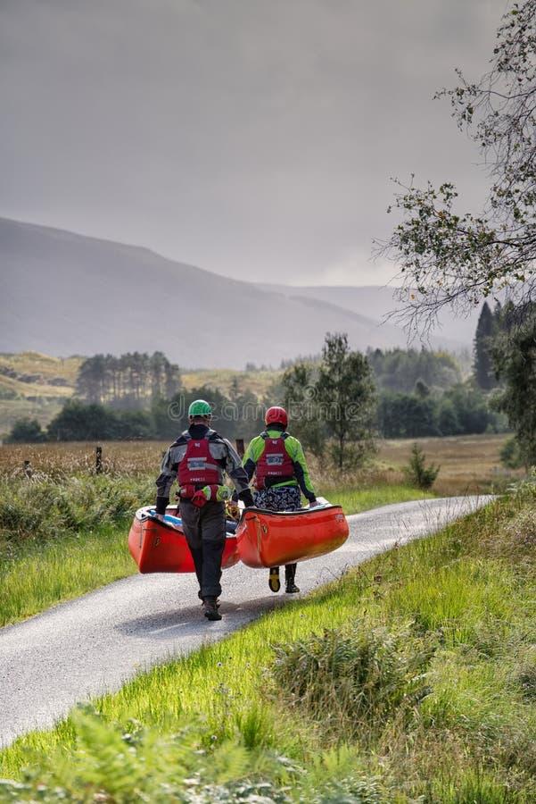 L'uomo e la donna portano due canoe lungo la strada della singola pista, Glencoe, Scozia immagine stock