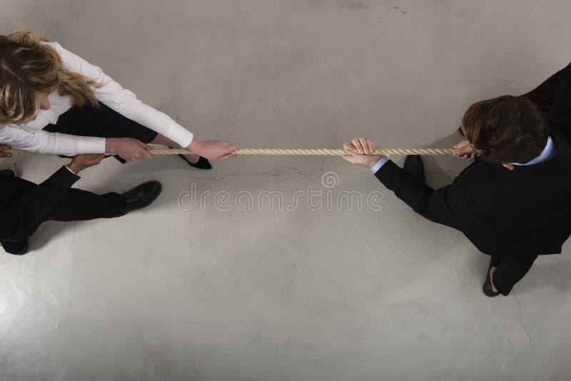 L'uomo e la donna rivali di affari competono per il comando tirando la corda fotografia stock