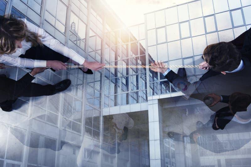 L'uomo e la donna rivali di affari competono per il comando tirando la corda Doppia esposizione fotografia stock