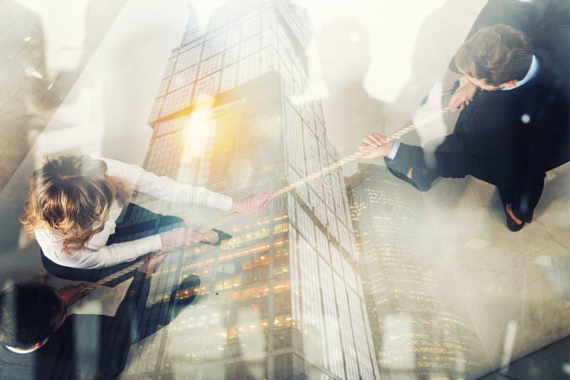 L'uomo e la donna rivali di affari competono per il comando tirando la corda Effetto di doppia esposizione fotografia stock