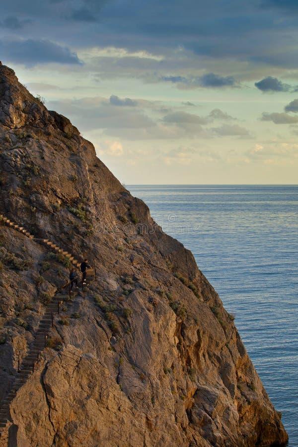 L'uomo e la donna scalano le scale sulla roccia fotografia stock libera da diritti