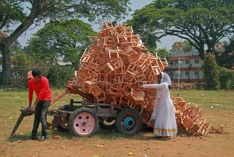 L'uomo e la donna stanno scaricando un carretto con carico dei panchetti fotografie stock libere da diritti