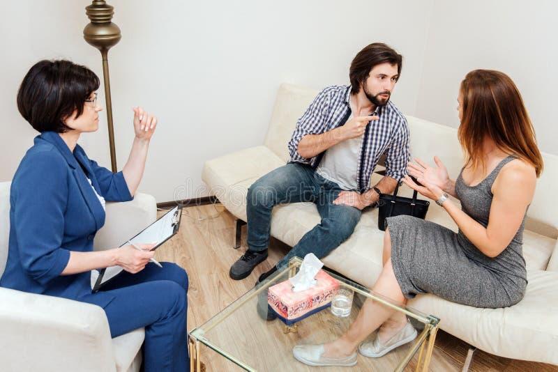 L'uomo e la donna stanno sedendo insieme e stanno guardando l'un l'altro Stanno discutendo Il tipo poointing sulla sua moglie immagine stock