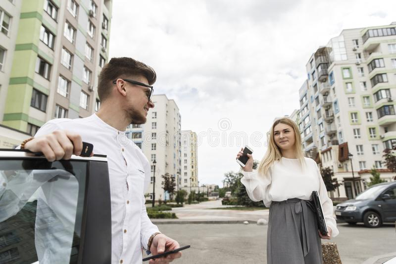 L'uomo e la donna stanno stando insieme esterni sulla via Tipo s che si appoggia la porta dell'automobile Sta tenendo il telefono fotografia stock
