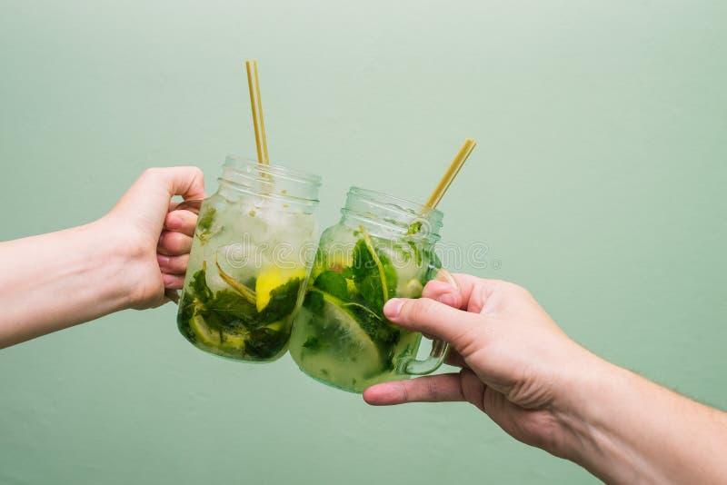 L'uomo e la donna stanno tenendo i cocktail Gli amici celebrano, dicono un saluto e bevono le bevande tropicali Concetto, festa o fotografie stock libere da diritti