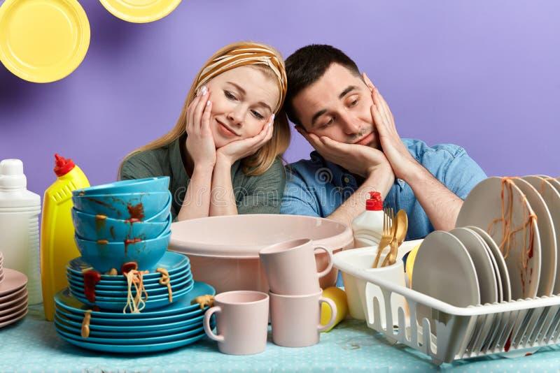 L'uomo e la donna turbati deprimenti non vogliono lavare i piatti dopo il partito fotografia stock libera da diritti