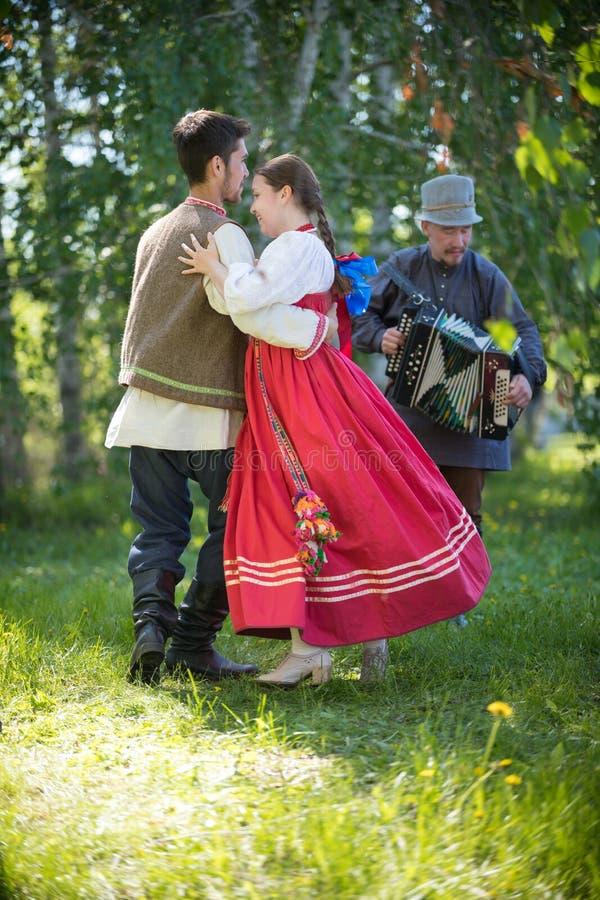 L'uomo e la donna in vestiti russi tradizionali stanno eseguendo le danze popolari russe e un uomo gioca una fisarmonica vicino fotografia stock libera da diritti