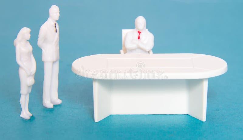 L'uomo e la ragazza dalle figure del giocattolo sono venuto all'ufficio ad ottenere un lavoro, il concetto dei posti vacanti Riso fotografia stock libera da diritti