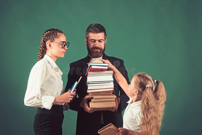 L'uomo e le ragazze dell'insegnante tengono il mucchio del libro a scuola Tempo della scuola delle sorelle e del padre in bibliot fotografia stock libera da diritti