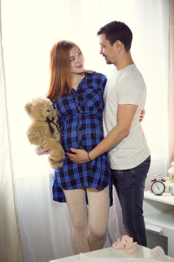 L'uomo e una giovane donna incinta stanno aspettando un bambino a casa b fotografia stock