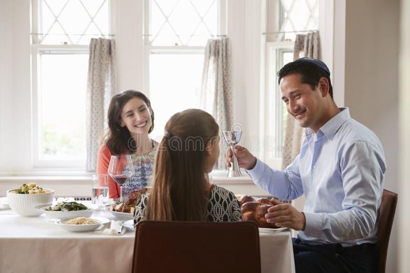L'uomo ebreo che tiene la tazza kiddish benedice la sua famiglia a Shabbat fotografie stock libere da diritti