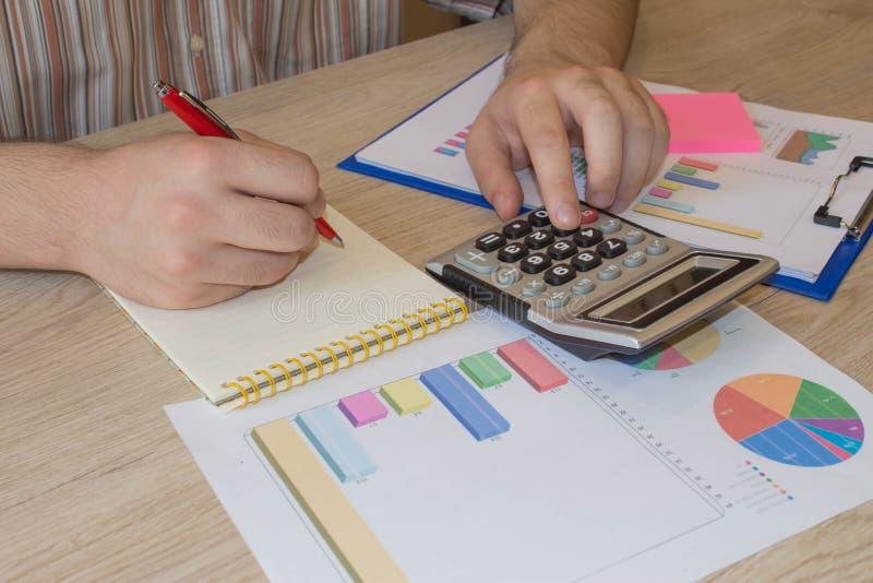 L'uomo ed il computer stanno utilizzando un calcolatore sulla tavola nella stanza dell'ufficio Concetto di affari e di contabilit fotografie stock