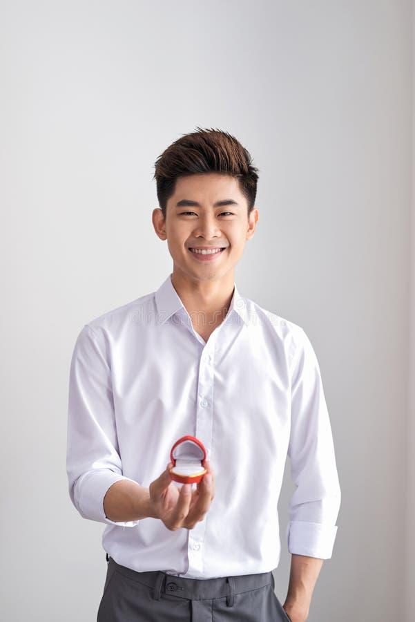 L'uomo elegante bello in una camicia bianca sta tenendo una scatola con un anello di fidanzamento e mostra in camera immagini stock