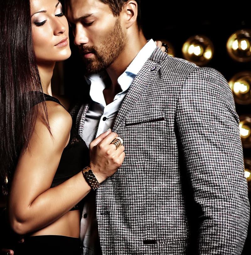 L'uomo elegante bello in vestito con la bella donna sexy che posa sullo studio nero accende il fondo immagine stock