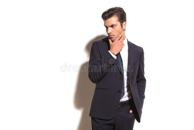 L'uomo elegante di affari che pensa e distoglie lo sguardo per parteggiare fotografia stock libera da diritti