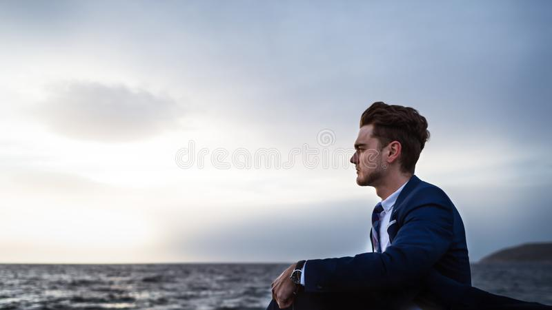 L'uomo elegante romantico in vestito si siede sui precedenti del mare e del cielo fotografia stock