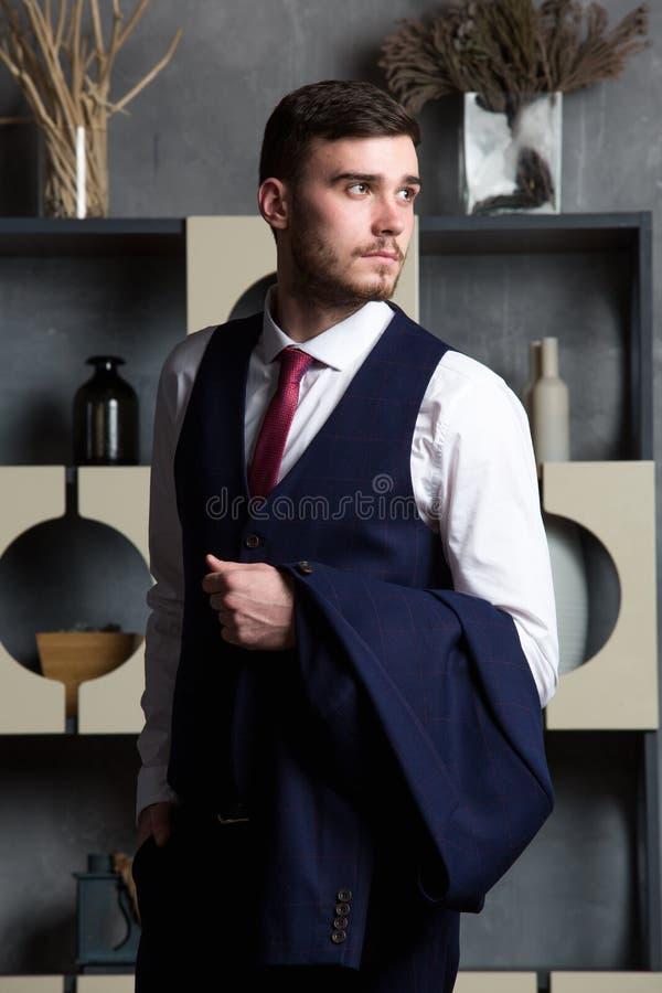 L'uomo elegante in un abito tre pezzi sta in studio interno immagini stock