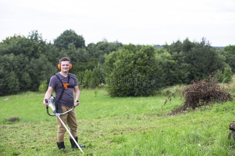 L'uomo elimina l'erba con un regolatore del gas della corda fotografia stock