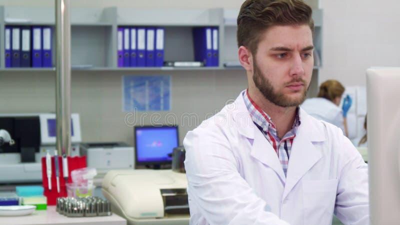 L'uomo esamina il monitor il laboratorio fotografie stock
