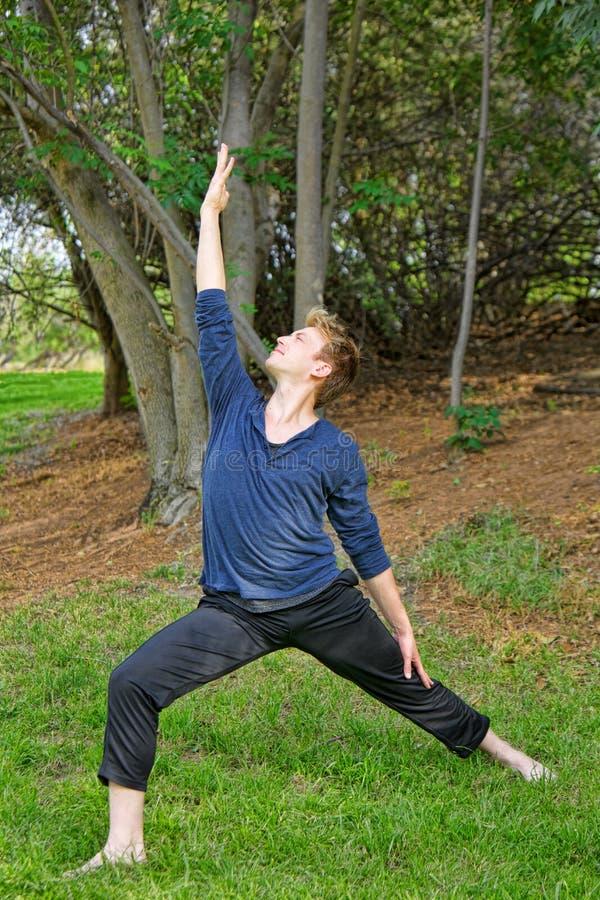 L'uomo esegue la posa inversa di yoga del guerriero in parco fotografie stock