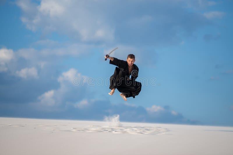 L'uomo espressivo salta con una spada giapponese, katana immagini stock libere da diritti