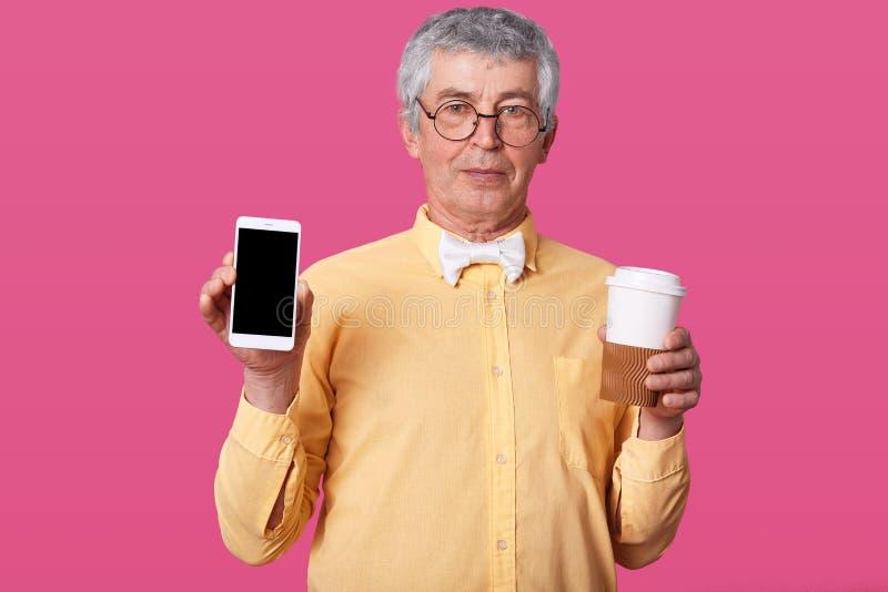 L'uomo europeo maturo serio calmo, la camicia gialla d'uso e la cravatta a farfalla bianca, tiene la tazza moderna di carta e del fotografie stock libere da diritti