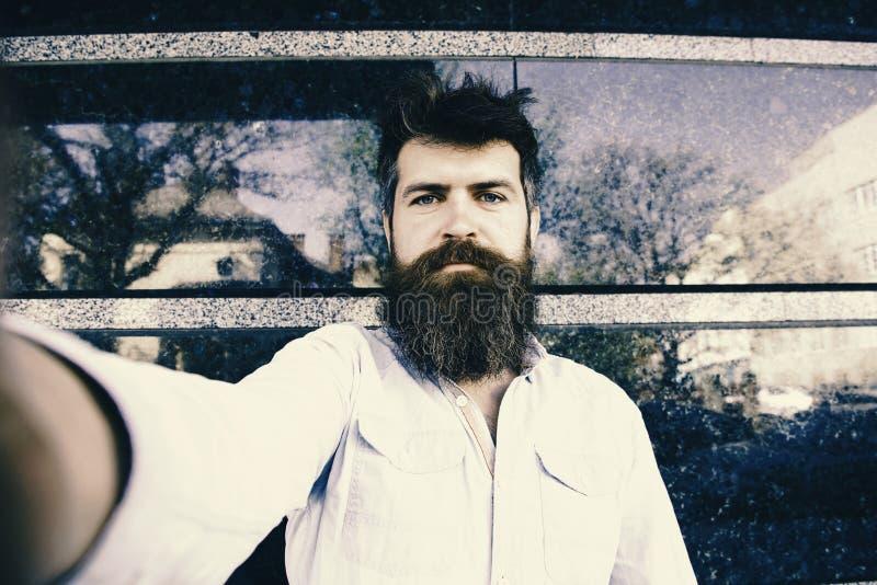 L'uomo fa i selfies Concetto di Vlogging Pantaloni a vita bassa, turista con capelli scompigliati e barba lunga che esamina macch fotografia stock