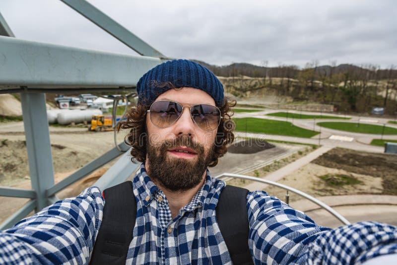 L'uomo fa i selfies Concetto di Vlogging Pantaloni a vita bassa, turista con capelli scompigliati e barba lunga che esamina macch fotografia stock libera da diritti