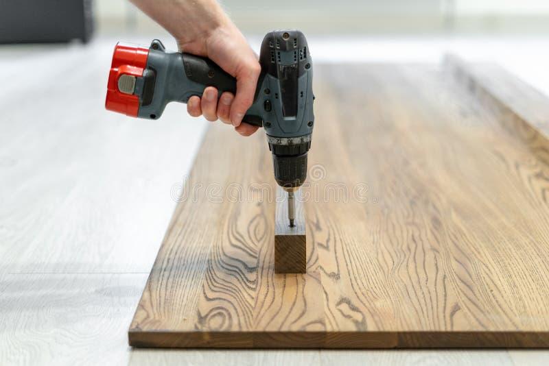 L'uomo facendo uso del cacciavite fissa la plancia sul piano d'appoggio di legno fotografia stock libera da diritti