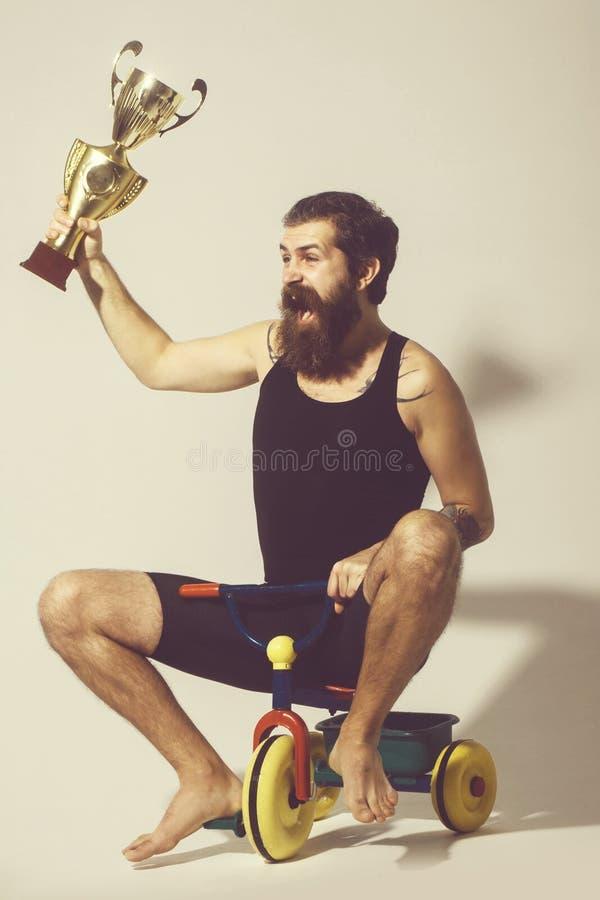 L'uomo felice barbuto tiene la tazza di campione dell'oro sul giocattolo della bicicletta fotografia stock libera da diritti