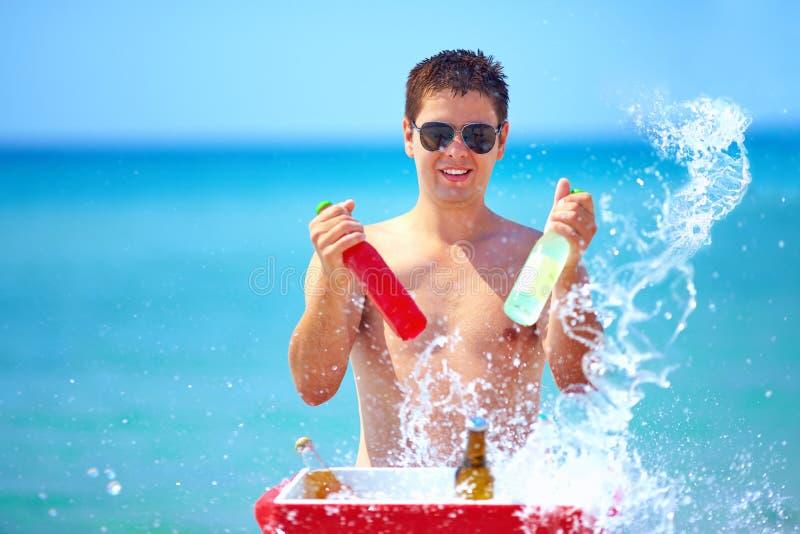 L'uomo felice con le bevande e la spruzzata dell'acqua sulla spiaggia fanno festa fotografia stock libera da diritti